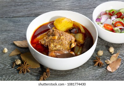 Masaman curry chicken in white bowl with cucumber and vegetables pickled sauce eat with curry / Halal food