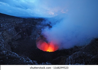 Masaya Volcano with visible lava pool and glowing exhaust fumes and gases in twilight, Masaya, Nicaragua, Central America.
