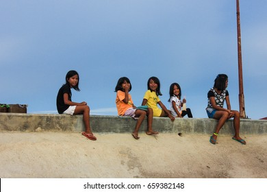 MASBATE, PHILIPPINES – MAY 28 2016: Unidentified girls stare from a pier in Masbate, Philippines.