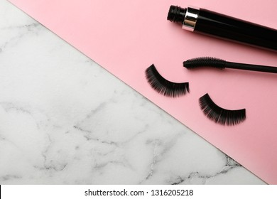 Mascara and artificial eyelashes on table. Space for text