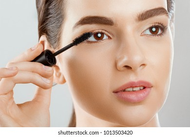 Mascara Closeup Of A Beautiful Young Woman A Face With A Beauty Makeup, Fresh Soft Skin Applying Mascara With Cosmetic Brush. Make-up And Cosmetics Concept.