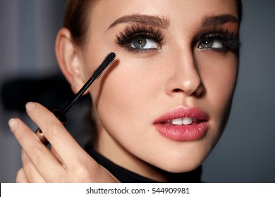 Mascara. Closeup Of Beautiful Young Woman Face With Beauty Makeup, Fresh Soft Skin And Long Black Thick Eyelashes Applying Mascara With Cosmetic Brush. Make-up And Cosmetics Concept. High Resolution
