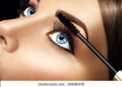 Mascara Makeup Applying closeup. Long Lashes closeup. Mascara Brush. Eyelashes extensions. Makeup for Blue Eyes. Eye Make up Apply