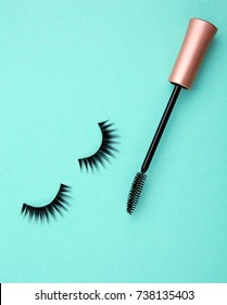 Mascara wand and false eyelashes on color background