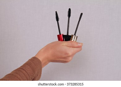 Mascara Wand Shapes. Woman holding different shapes of mascara wand close up