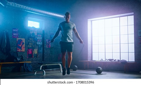 Masculine Athletic Young Man Exercises with Jumping Rope in a Loft Style Industrial Gym. He's Doing His Intense  Fitness Training Program. Facility has Motivational Posters on the Wall. - Shutterstock ID 1708015396