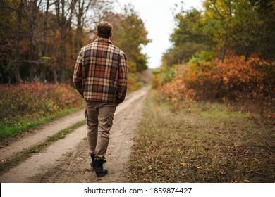 Masculine caucasian man strolling in autumn forest - Shutterstock ID 1859874427