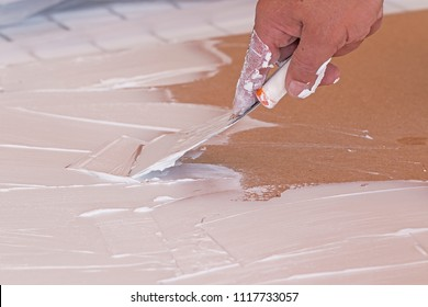 A masculine hand spreading plaster with a spatula on a surface.