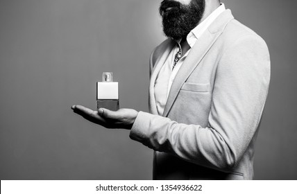 Masculine perfume, bearded man in a suit. Male holding up bottle of perfume. Perfume or cologne bottle and perfumery, cosmetics. Black and white.