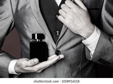 Masculine perfume. Man perfume, fragrance. Male fragrance and perfumery, cosmetics. Man holding up bottle of perfumery. Cologne bottle. Black and white.