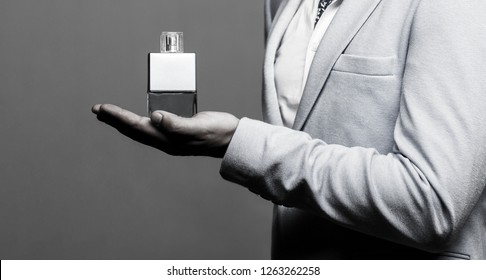 Masculine perfume, man in a suit. Man perfume, fragrance. Male holding up bottle of perfume. Black and white.