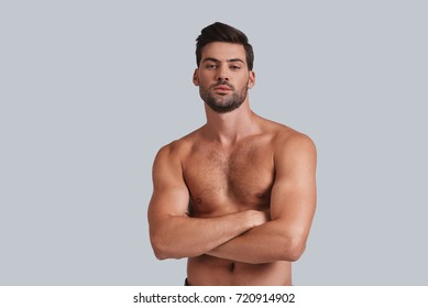 Masculinity and charisma. Handsome young man keeping arms crossed and looking at camera while standing against grey background