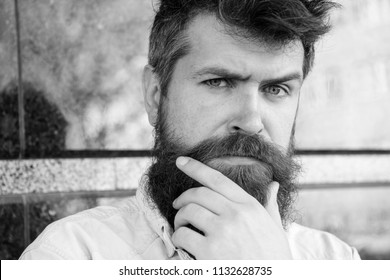 Masculinity concept. Guy looks suspicious. Hipster with tousled hair touches beard while looking into distance. Man with beard and mustache on thoughtful, pensive face, black marble background.
