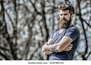 Masculinity and manliness. Man attractive bearded hipster posing outdoors. Confident posture of handsome man. Guy masculine appearance with long beard. Barber concept. Beard grooming. Beard care.
