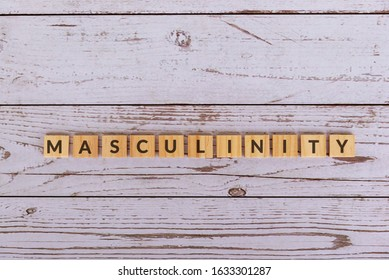 Masculinity text on wood blocks, wooden background.