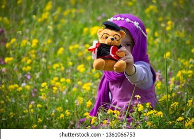 Masha and the bear.Little girl with teddy bear on field