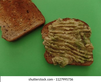 Mashed avocado on toast against a neon green background