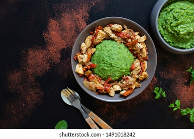 Mashed potatoes with green peas and corn served with chicken and vegetable stew. African cuisine, Kenyan cuisine, a traditional dish called mukimo. Top view, copyspace