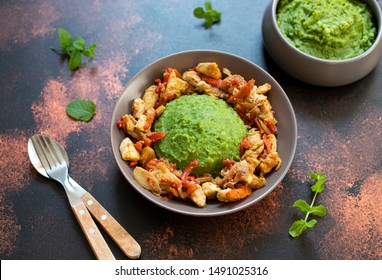 Mashed potatoes with green peas and corn served with chicken and vegetable stew. African cuisine, Kenyan cuisine, a traditional dish called mukimo or irio. Close-up