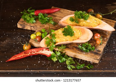 Mashed sweet potato with pepers chilli, tomatoes and greenery on a dark wooden board background. Horizontal.