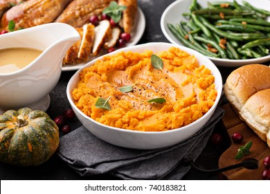Mashed sweet potatoes with butter and cinnamon on Thanksgiving table with turkey and green beans