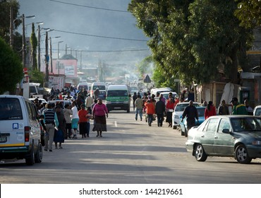 Masiphumelele Township,Cape Town,South Africa - June 30, 2013: Busy street scene with people and cars at entrance to township.