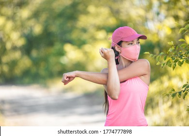 Mask covid-19 runner woman stretching arms before cardio workout on outdoor summer park run jogging wearing face covering protection for coronavirus.