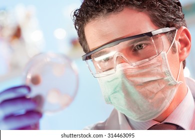 Mask and goggles protected life science researcher observing potentially infectious cells in petri dish. Focus on scientist's eye. Health care and biotechnology concept.