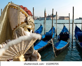 mask and gondola boats waiting for turists in the Venice