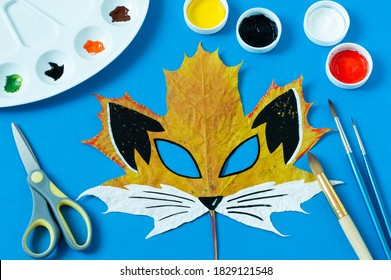 Mask painted on maple leaf. Drawing on autumn leaves. Fox mask for autumn carnival or party. Art project for children. DIY concept