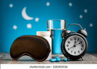 Mask, pills and alarm clock on night sky background. How to beat insomnia and restore sleeping routine.