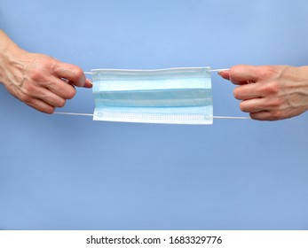 mask - to prevent the spread of the virus . Hands holding a medical mask on a blue background . copy  space.