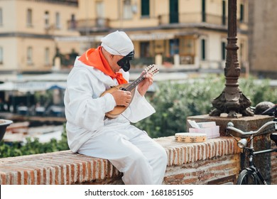 The mask of Pulcinella (Punchinello) plays the mandolin on the Naples promenade, Italy - Shutterstock ID 1681851505