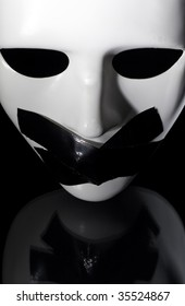 mask shot from above with masking tape on it's mouth ,on reflective surface,clipping path available