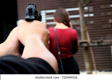 Mask thief in balaclava with holding gun ,Outlaw bad man  hold a gun pointing the target at bathroom , robber in black hood holding gun and pointing to victim that picture select focus