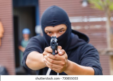 Mask thief in balaclava with holding gun.bad man hold a gun pointing the target at restroom. robber in black hood holding gun and pointing to a person.