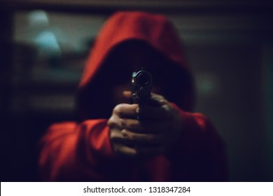 Mask thief holding gun. Outlaw bad man hold a gun pointing the target at restroom. robber in red hood holding gun and pointing to a person, selected focus with noise and grain effect