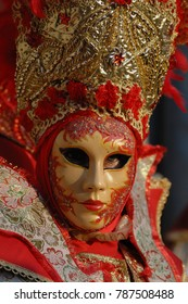 mask of venice carnival with a rich red hat and gold