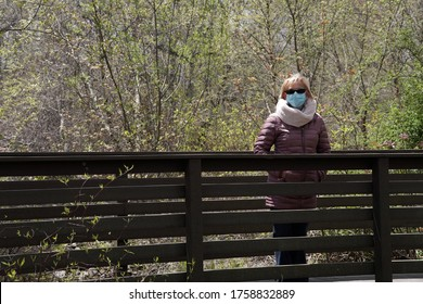 A masked blonde Caucasian woman pauses on a bridge during the Coronavirus Pandemic.
