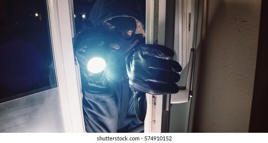 Masked burglar entering amd breaking into a house window with  flashlight