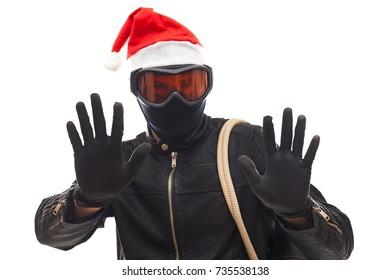 Masked burglar with santa claus cap holding his sack, posing on isolated background