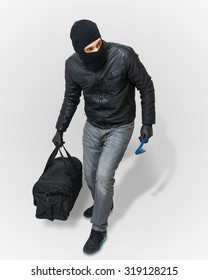 Masked burglar or thief with balaclava is creeping with black bag on white background.
