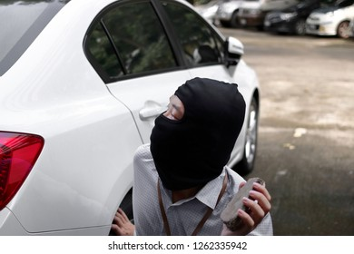 Masked burglar wearing a balaclava holding little stone ready to burglary against car background. Insurance crime concept.