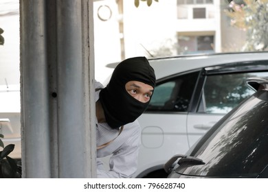 Masked burglar wearing a balaclava ready to burglary against car background. Insurance crime concept.
