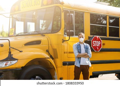 masked bus driver looking at camera outside the elementary school