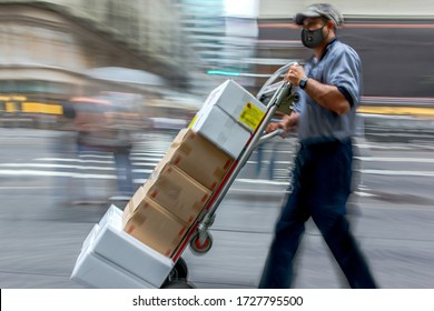 masked business people in a city, delivery goods with dolly by hand, purposely motion blur