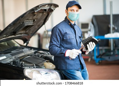 Masked car mechanic holding a jug of motor oil during coronavirus pandemic - Shutterstock ID 1708466818