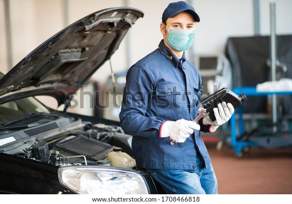 Masked car mechanic holding a jug of motor oil during coronavirus pandemic