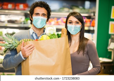 Masked couple holding a shopping bag full of food in a supermarket during coronavirus pandemic