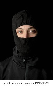 A masked criminal dressed in black